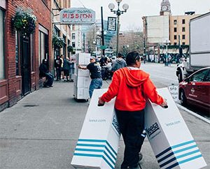 guy carrying two leesa mattresses to charity