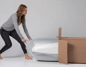 lady pulling the luxi mattress out of the shipping box to review it