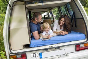 people smiling on a mattress in a minivan
