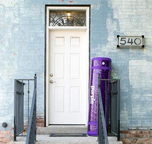 A purple mattress rolled up for shipping