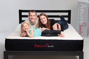 a family smiling on the mattress