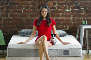 a reviewer sitting on the kutson mattress with a little dog